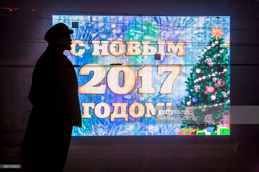 "Lenin statue silhouette over a large screen saying ""Happy New Year 2017"" in the center of Donetsk city, Ukraine on 31 December 2016. (Photo by Celestino Arce/NurPhoto)"