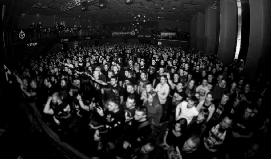 Imagen del Asgardsrei V, con parte de los asistentes realizando el saludo nazi. Al fondo a la derecha, pancarta de Reconquista. A la izquierda, el emblema del Russki Tsenter, el Centro Ruso ultraderechista en Ucrania